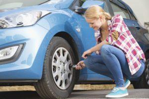 Femme vérifiant ses pneus